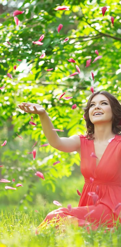 Woman in Red Dress sitting on Green Grass stretching out Hands and catching the falling Rose Petals.