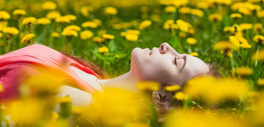 Root Chakra Meditation: Woman in Red Dress lying in the Field of Yellow Flowering Dandelions.