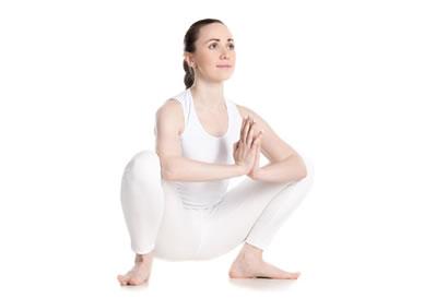 Root Chakra Yoga Pose: Woman assuming Yoga Crow Position