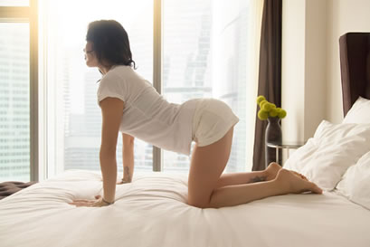 Woman on Bed assuming the Yoga Cat Pose